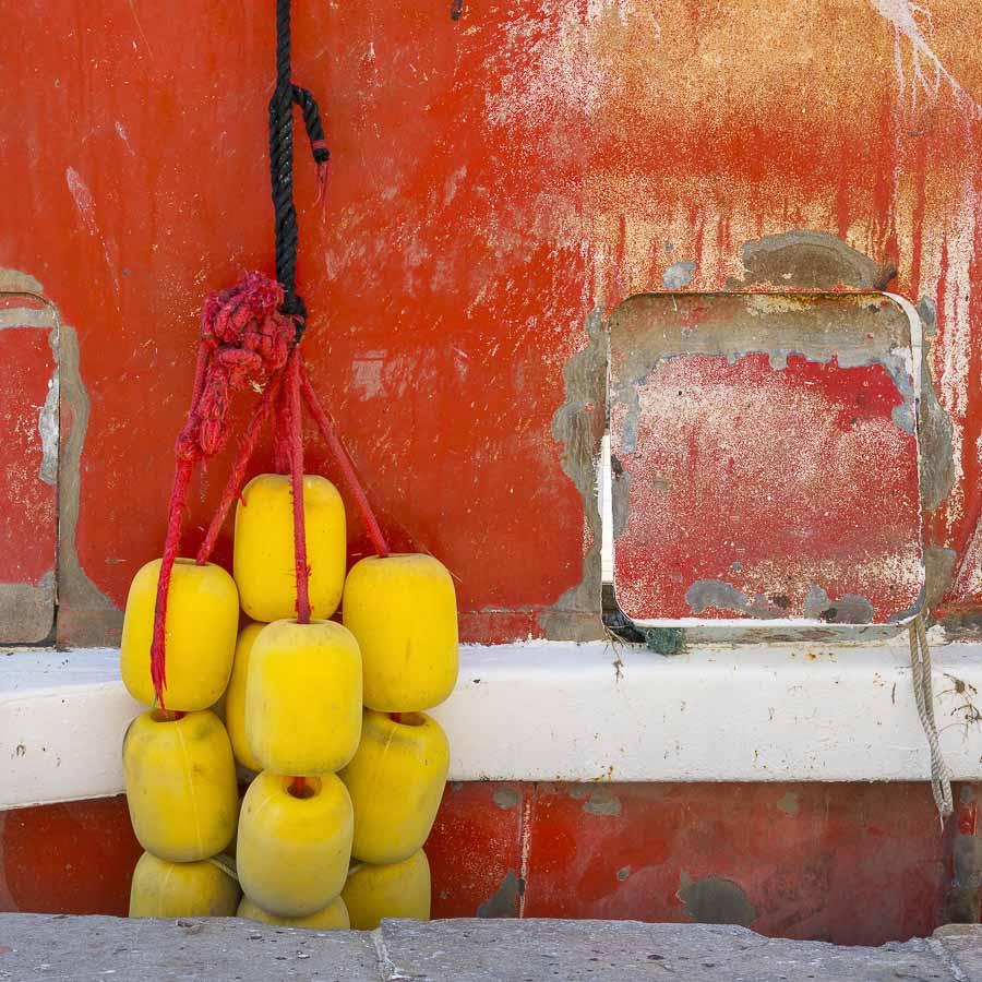 Détail d'un bateau rouge sur le bord du canal à Sète dans l'Hérault des flotteurs jaunes entre le bateau et le quai