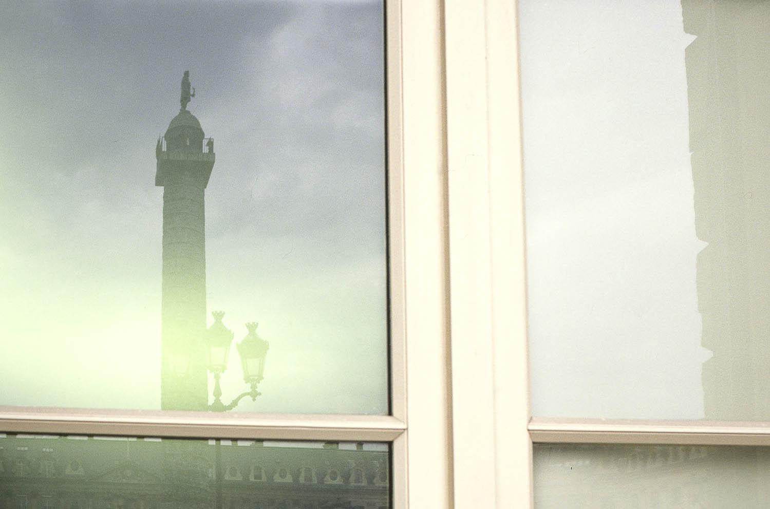 Place Vendôme premier arrondissement à Paris. Photo d'une fenêtre reflétant la colonne de la place Vendôme