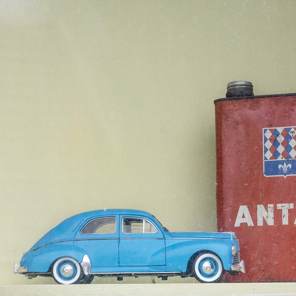 Détail dans une vitrine d'un ancien garage mécanique automobile voiture miniature ancien de collection bidon d'huile de marque Antar à Ouzouer-le-Doyen