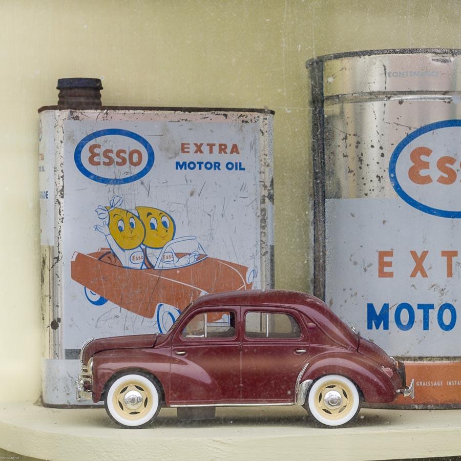 Détail dans une vitrine d'un ancien garage mécanique automobile voiture miniature ancien de collection bidon d'huile de marque Esso à Ouzouer-le-Doyen