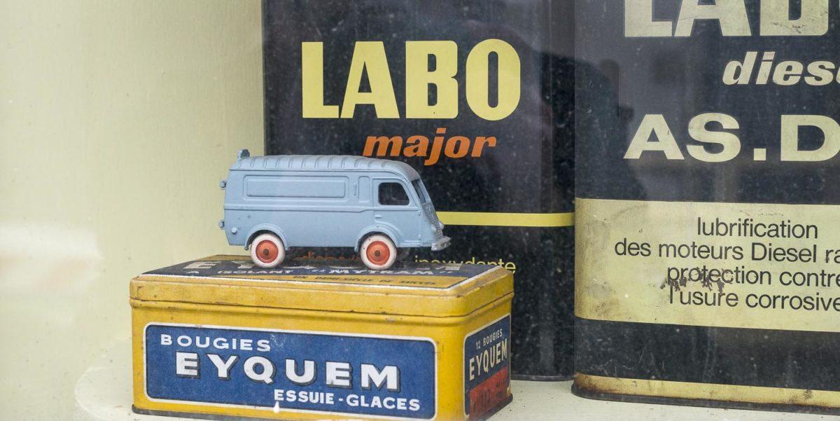 Détail dans une vitrine d'un des anciens garages automobiles voiture miniature ancien de collection bidon d'huile de marque Labo à Ouzouer-le-Doyen